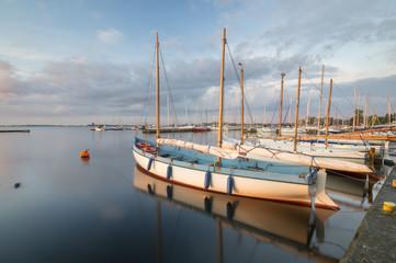 Sailing boats in marina at sunset.