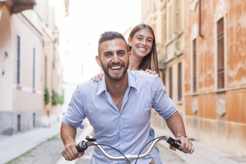 young loving couple cycling through the city