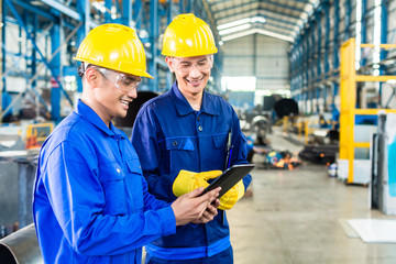 Two workers in production plant as team