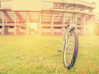 Vintage style photo of the retro bicycle in summer grass field w