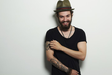 Smiling Hipster boy.handsome man in hat.Brutal bearded man with tattoo