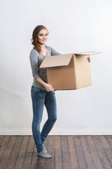 Young and beautiful woman with a big box. Moving and shopping concepts.