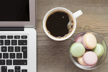 Laptop, cup of coffee and cookies on the wooden background