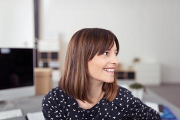 mitarbeiterin im büro schaut lächelnd zur seite