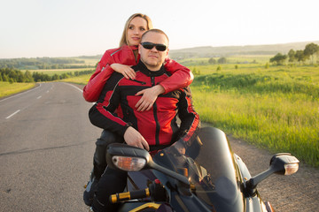 biker man and woman sitting on a motorcycle.