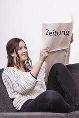 Frau liest sitzend eine Zeitung