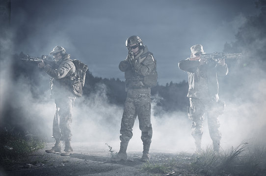 Men with rifle aiming in battlefield at night