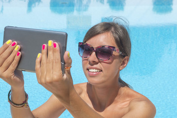 Young girl making selfie by the pool with a tablet