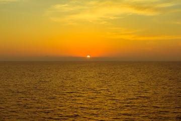 Scenic view of beautiful sunset above the sea with silhouette of island