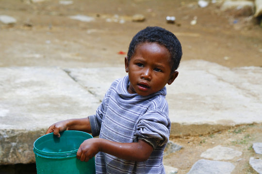 Poor malagasy boy carrying plastic water bucket - poverty