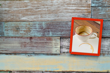 Red wooden frame with coffee cup hanging on a wooden board