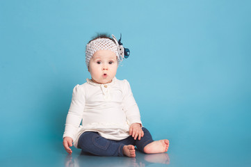Cute baby girl sitting in room over blue. Wearing trendy dress. Looking surprised at camera. Childhood.