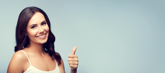 Portrait of happy brunette woman showing thumb up gesture, with