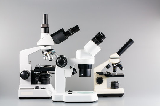 Monocular, binocular and trinocular microscopes on grey backgrou