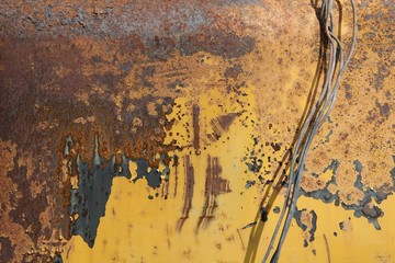 old rusty metal wire on a background of rusty metal surface painted with yellow paint, texture, background