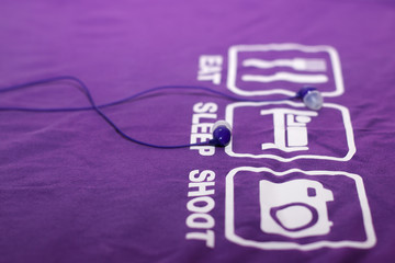 Vacuum blue headphones lying on purple T-shirt