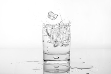 Splashing of water with ice in glass