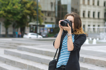 Woman with a camera photographs the city