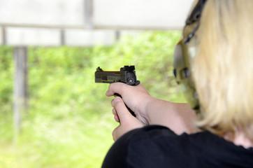 Blonde Frau mit Gehörschutz und Pistole