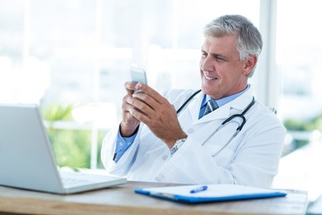 Smiling doctor sitting at his desk and texting