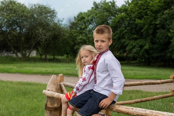 Children in ukrainian traditional clothes on the hedge