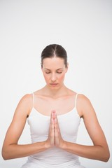 Fit woman meditating with hands crossed
