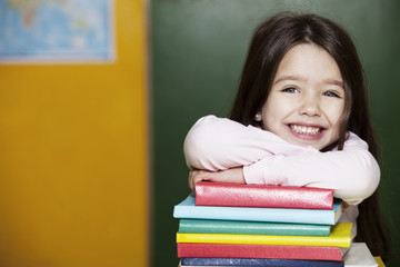 Happy little girl with books in school