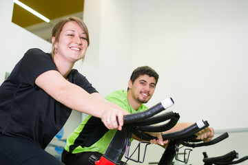 man and woman with stationary bicycle in gym