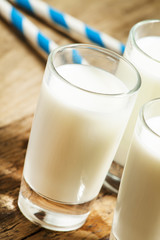 Three glasses of fresh milk on old wooden table in rustic style,