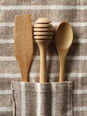 Wooden spoon and fork on pattern towel background