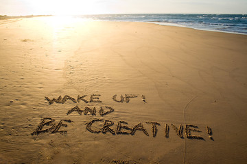 Wake up and be creative! Creative motivation concept written in the sand at the beach.