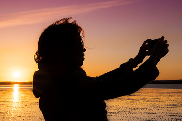 Beautiful young woman taking picture of herself, selfie, on a beach during sunset.