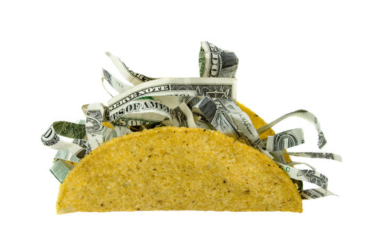 Shredded Money Taco Concept – A crispy taco shell filled with shredded money. Concept for the price of food, expensive eating, and more. Isolated on white with clipping path.