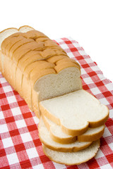Whole Loaf of Sliced White Bread – Sliced white bread on a red checked tablecloth.