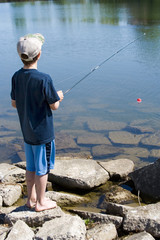 Young Boy Fishing – A young boy fishes at the lake.