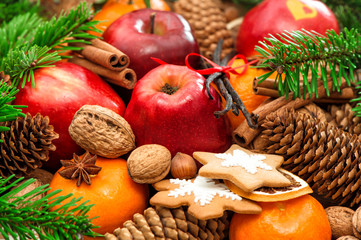 Christmas food background. Apple and mandarin fruits, walnuts, c