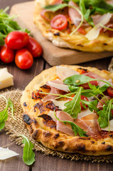 Italian pizza with parmesan cheese, prosciutto and arugula
