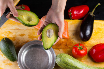 chef slicing the avocado closeup on a wooden board