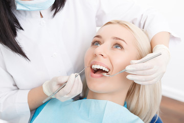 Woman having her teeth examined by dentist