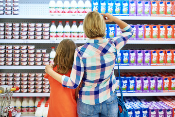 Mother and daughter choosing dairy products