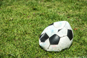 Deflated soccer ball on grass. Soccer concept.