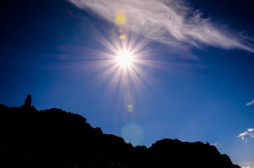 Sun Star on a Blue Sky over a Mountain Silhouette
