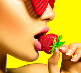 Sexy woman wearing glamour red sunglasses eating strawberry