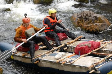 Two men on a makeshift catamaran raft on the northen river.