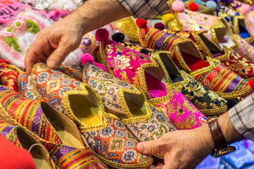 Colorful turkish slippers and shoes for sale on bazaar market, with hand movement of a buyer