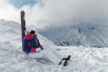 Young woman skier against a wonderful winter mountains background
