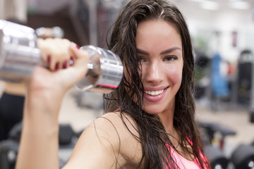 Young female working out with dumbbells in a gym