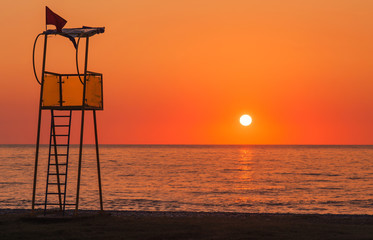 Lifeguard rescue tower on sea beach at sunset