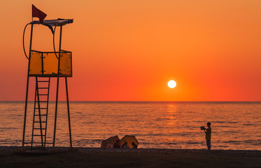 Lifeguard rescue tower on sea beach at sunset and child with boo