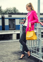 Beautiful modern girl with a mobile phone on the platform